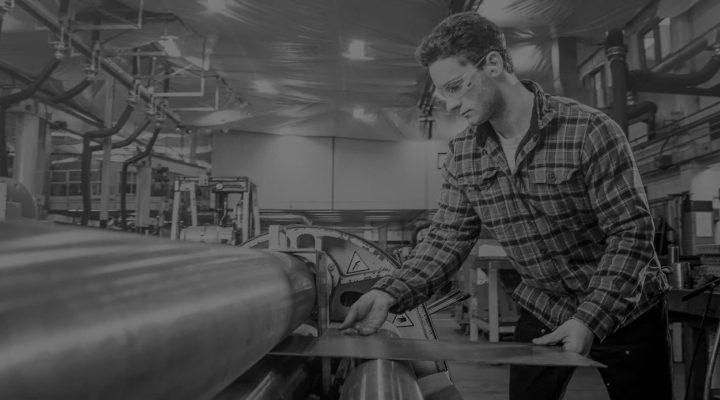 Man with plaid shirt flattening sheet metal on a rolling machine