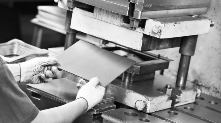 worker at manufacture workshop operating metal press machine